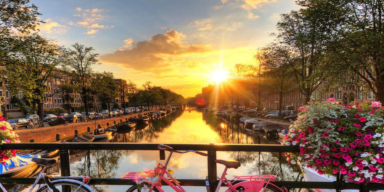 https://active-voyages.fr/wp-content/uploads/2020/03/Beau-lever-de-soleil-sur-Amsterdam-Pays-Bas-avec-des-fleurs-et-des-vélos-sur-le-pont-au-printemps-1280x640.jpg